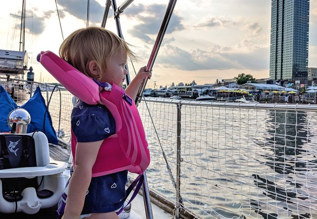 toddler sailing while wearing a baby life jacket