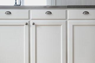 Detalj av de vita köksluckorna i ask.