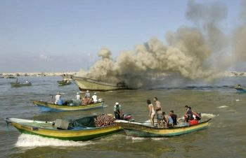 Palestinian fishermen gather around a fishing boat after it was hit by Israeli army naval fire at Gaza's seaport.