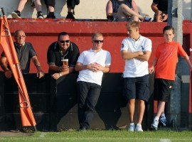 Paul Scholes (centre) and Phil Neville (2nd right) watch Salford City playing against Stalybridge Celtic.