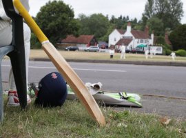 A player waiting to bat relaxes during a village cricket match between Tilford and Grayswood being played at Tilford Green in Waverley, Surrey.