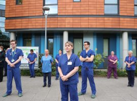 Staff stand outside Salford Royal Hospital in Manchester during a minute's silence to pay tribute to the NHS staff and key workers who have died during the coronavirus outbreak. Image Credits - PA Images/Peter Byrne