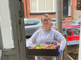 Volunteer for Humans MCR, Lorna, delivering service with a smile. Copyright: Lewey Hellewell.