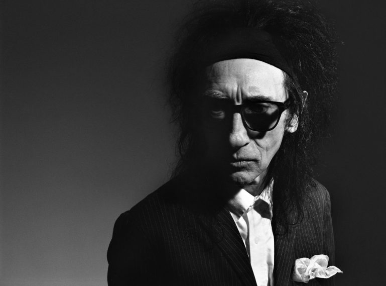 John Cooper Clarke stands to the right side of the picture, a white handkerchief poking out of his suit jacket pocket. He is wearing dark rimmed glasses and has jet black messy hair. I Wanna Be Yours