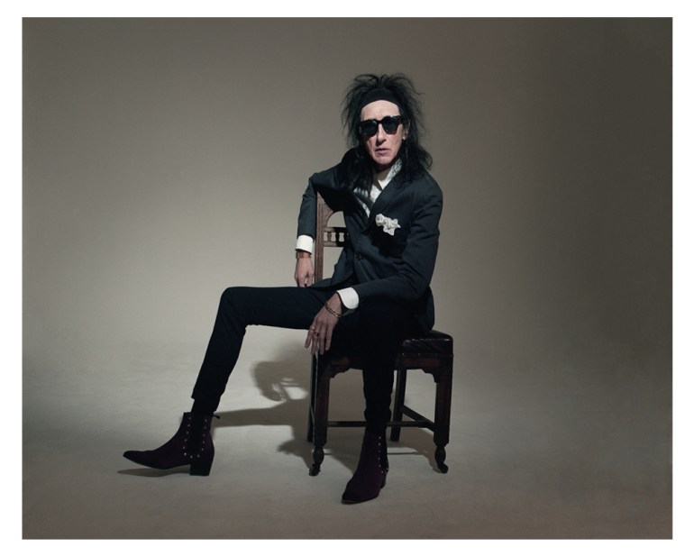John Cooper Clarke sits in an old wooden chair, dressed in his trademark black suit, white shirt, along with dark rimmed glasses and his dark messed up hair leading to one of his many nicknames, Johnny Clarke, the name behind the hairstyle.