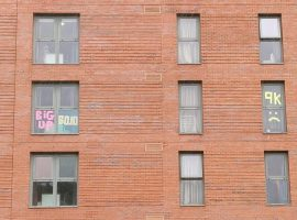 Some messages written in post-it notes in the windows of Peel Park Quarter's Lowry building. Image credit: Matthew Lanceley