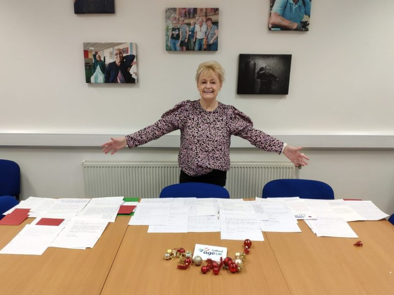 Age UK Salford's Home Services Coordinator distributing letters image.