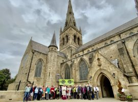 Right Reverend John Arnold and parishioners from Salford hold the 'Eyes of the World' banner outside of Salford Cathedral. Photo Credit: Holly Jones/Diocese of Salford