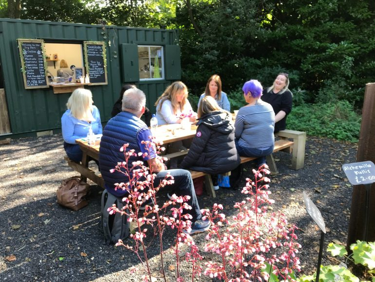 People relaxing Cleavley Community Forest Garden cafe Permission to use from Ian Bocock
