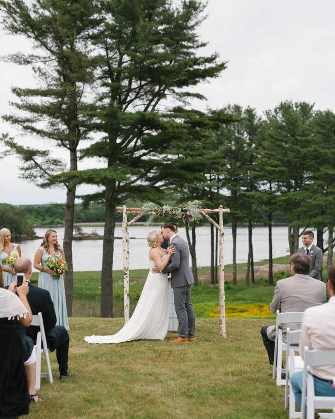 Newly married couple kiss at outdoor wedding in Maine