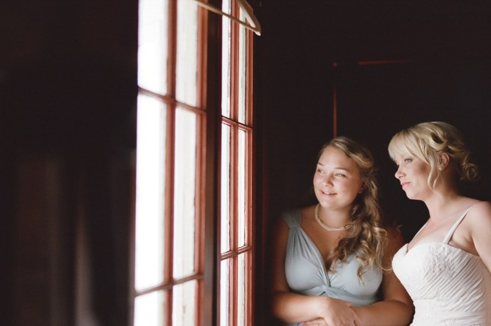 Bride and her friend look out the window into the sunshine