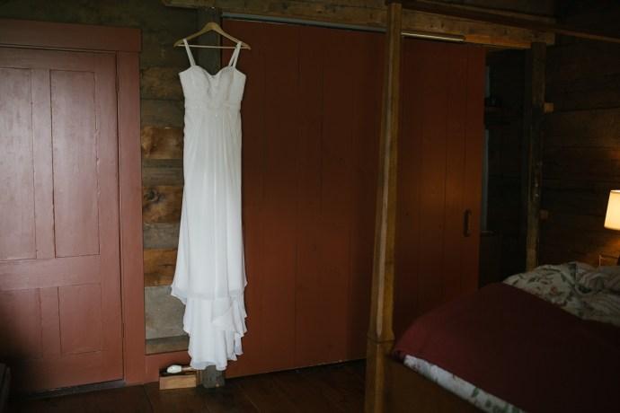elegant wedding dress hanging from doorway