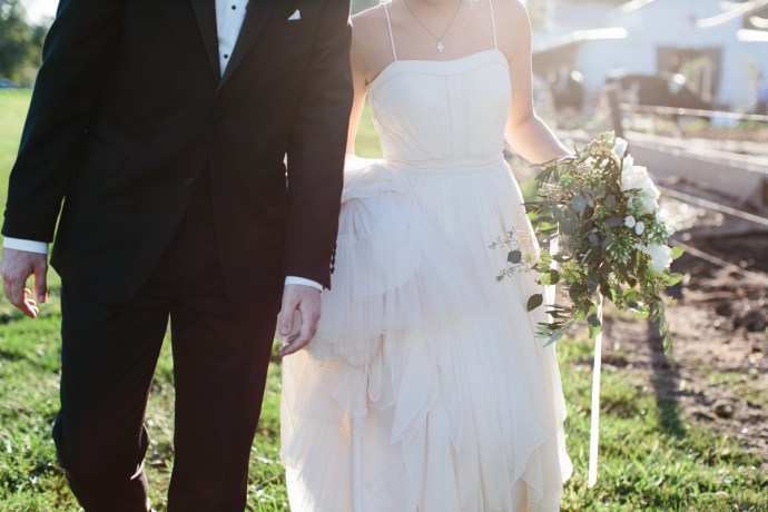 sun highlights a close up of bride's dress and groom's suit