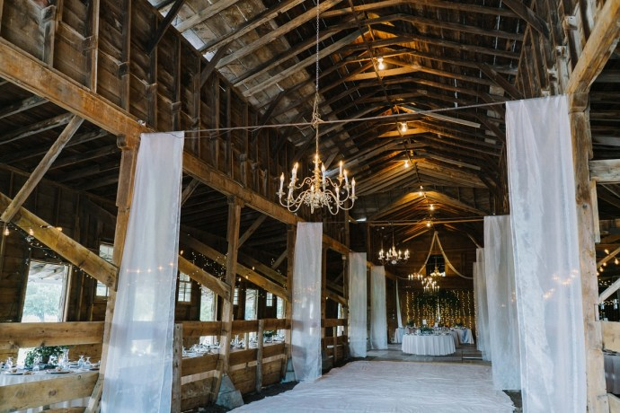 Majestic and vintage barn wedding with chandeliers and curtains