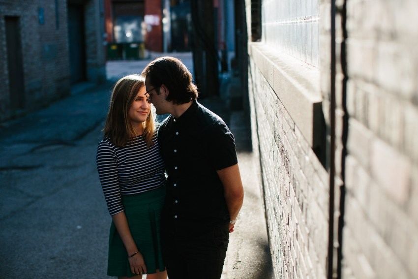 Engaged couple pose in alley