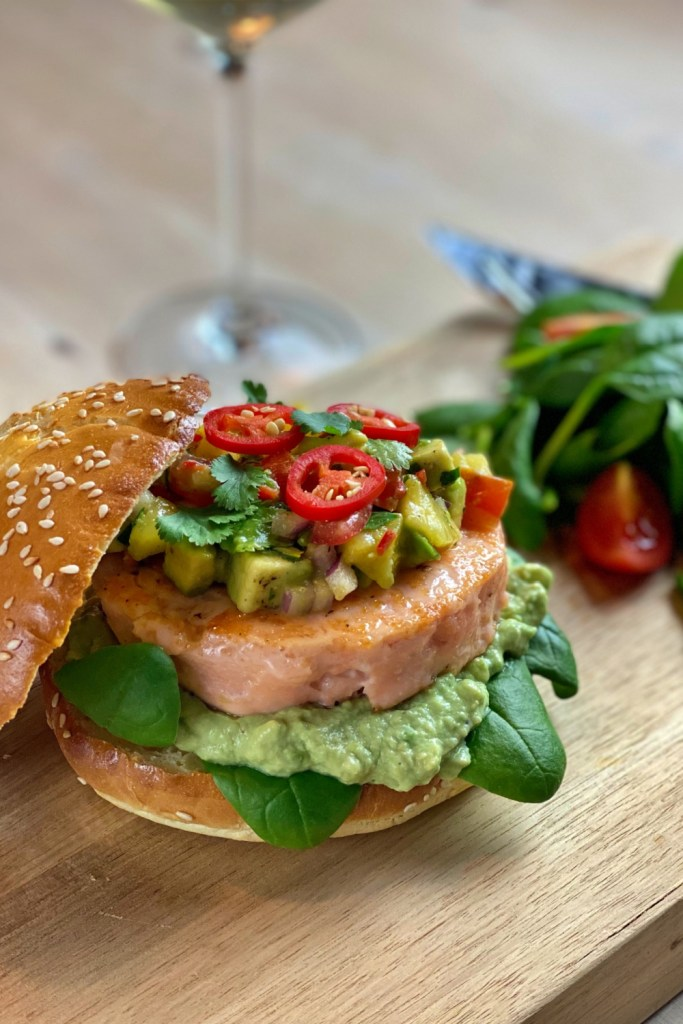 The salmon burger is served with mild avocado cream and sweet and spicy salsa. It is a really tasty dish that the whole family loves!