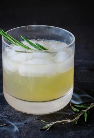 Image of cocktail glass with a rye bourbon cocktail and a smoky sprig of rosemary