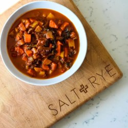 Image of Beef and Tomato Stew on a wooden cutting board with the Salt and Rye logo, on a white countertop