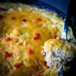 Image of a skillet of Cheesy Grits Casserole. The casserole has grits, cheese (duh), eggs, sausage and pimentos.