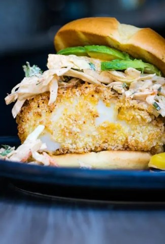 Over Stuffed air fried cod sandwich topped with chili mango slaw and avocado