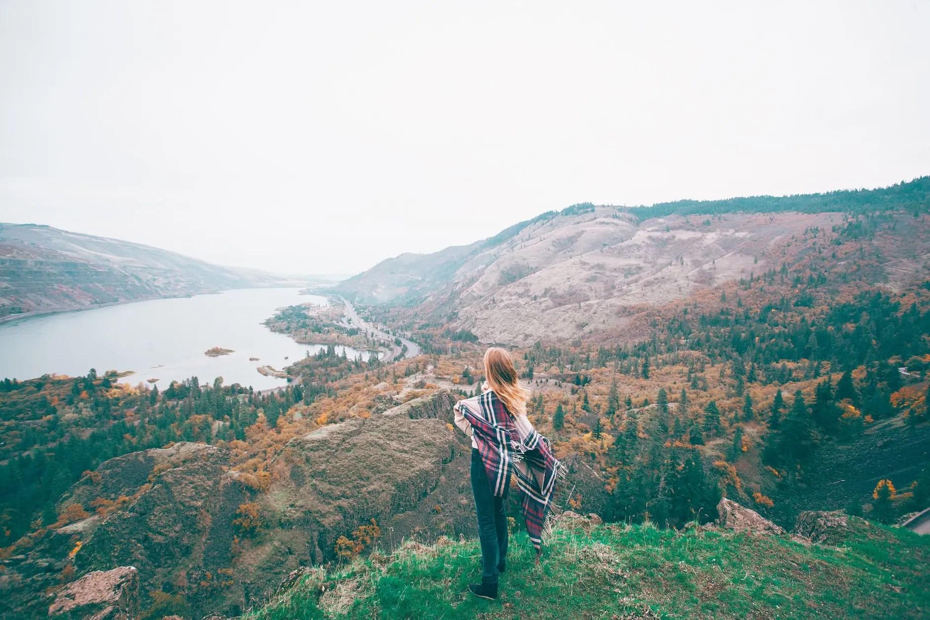 unrecognizable female tourist admiring lake in mountains