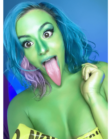 Selfie of Jenn sticking out her tongue. Her skin is tinted green and her tongue is edited so it's extra long. She has blue, green, and pink hair and her left hand is up by her shoulder.