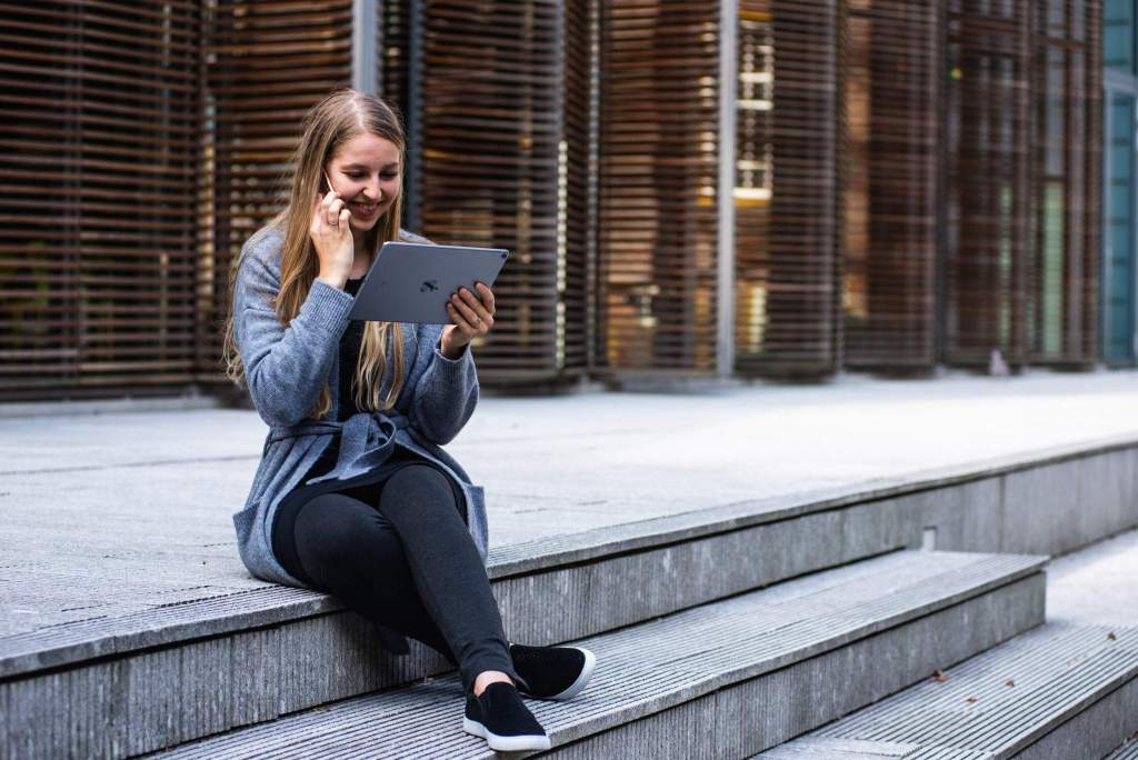 (Woman is sitting outside on the steps of a building. She is using her iPad).