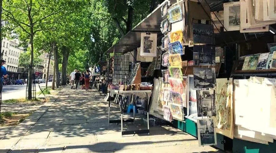 Bouquinistes de Paris lined up along the Seine - in the iconic green boxes they are offering vintage books, paintings and souvenirs - Maybe you can even find some romantic books set in Paris?