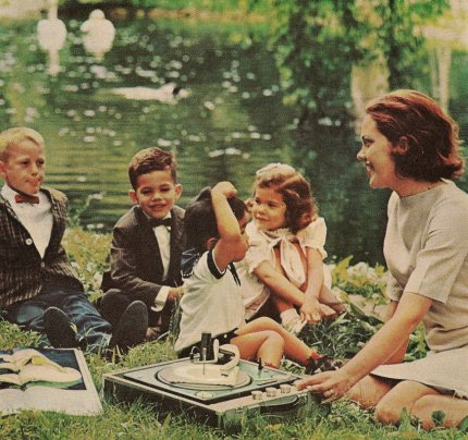 a picknicking family of the 60ies listening to music