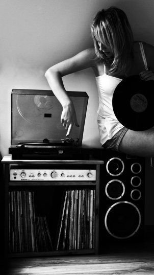 woman sitting on stereo system playing a vinyl