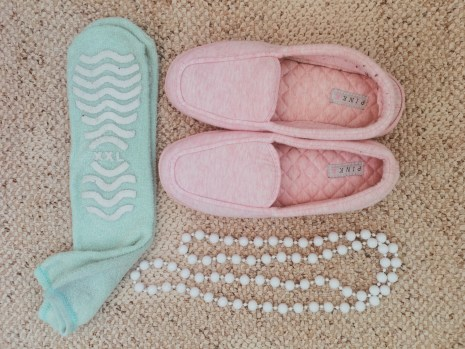 Flatlay picture of green hospital socks, pink slippers and long white beaded neclace
