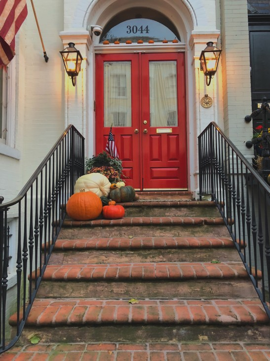 Georgetown, DC house with red doors, lanterns and pumpkins on steps