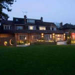 Garden and house at night with external lighting