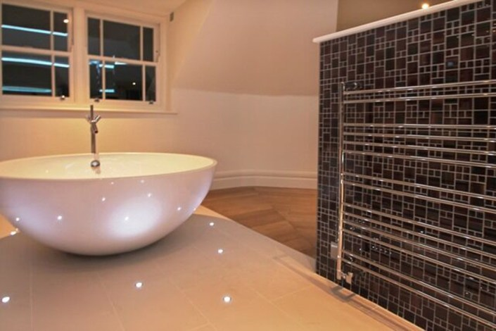 Bathroom lighting with towel rail by Sam Coles Lighting