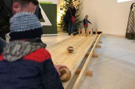 Die Kinder haben Spaß mit der Holzkegelbahn.