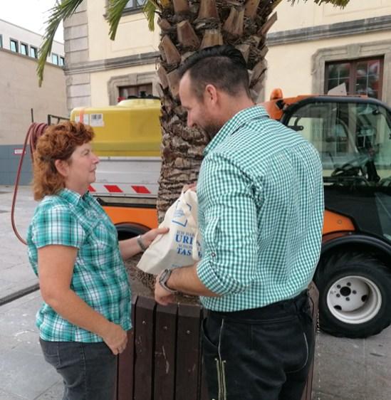 Florian Tatzel überreicht einer städtischen Mitarbeiterin ein kleines Präsent