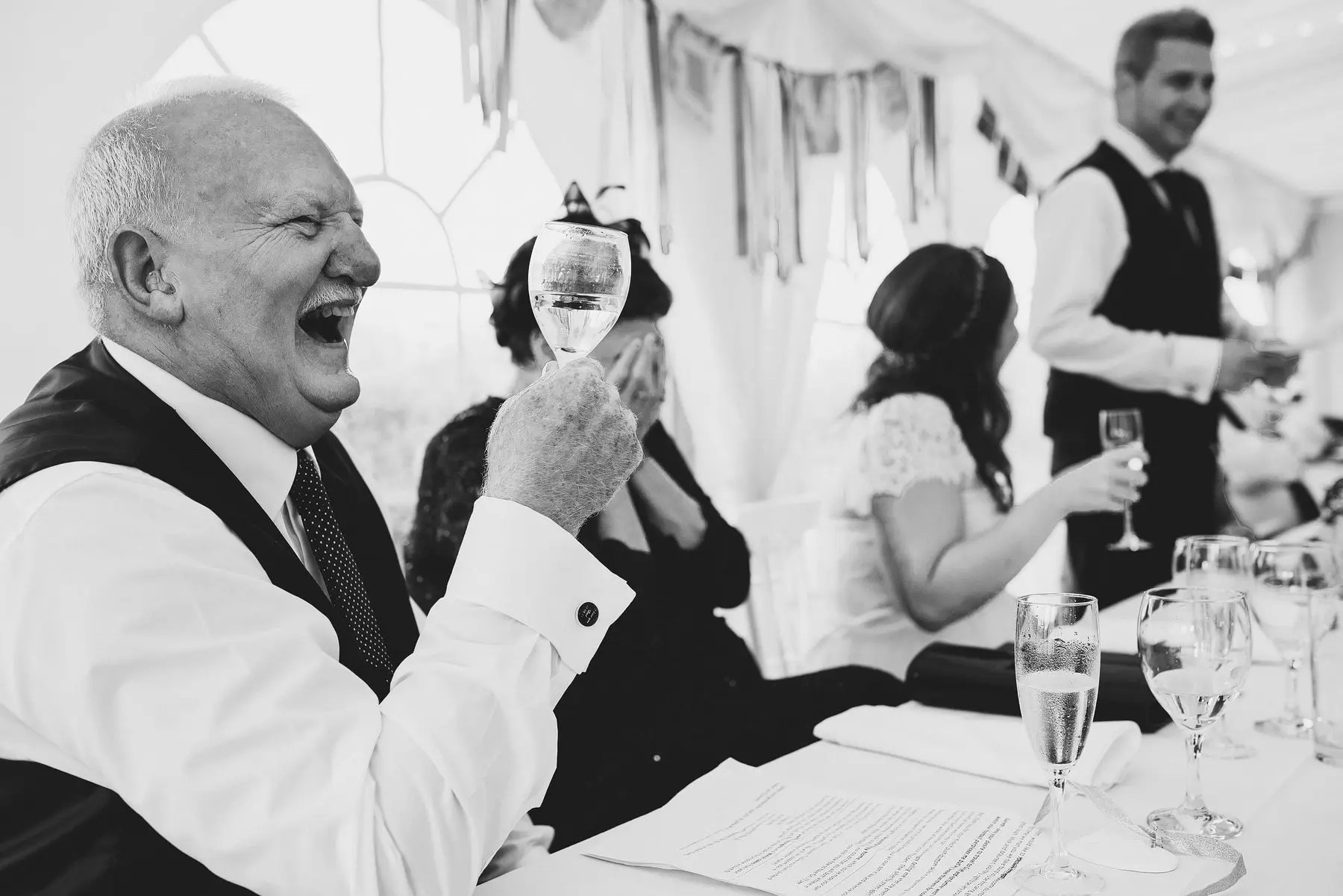 father of the bride laughing during speeches