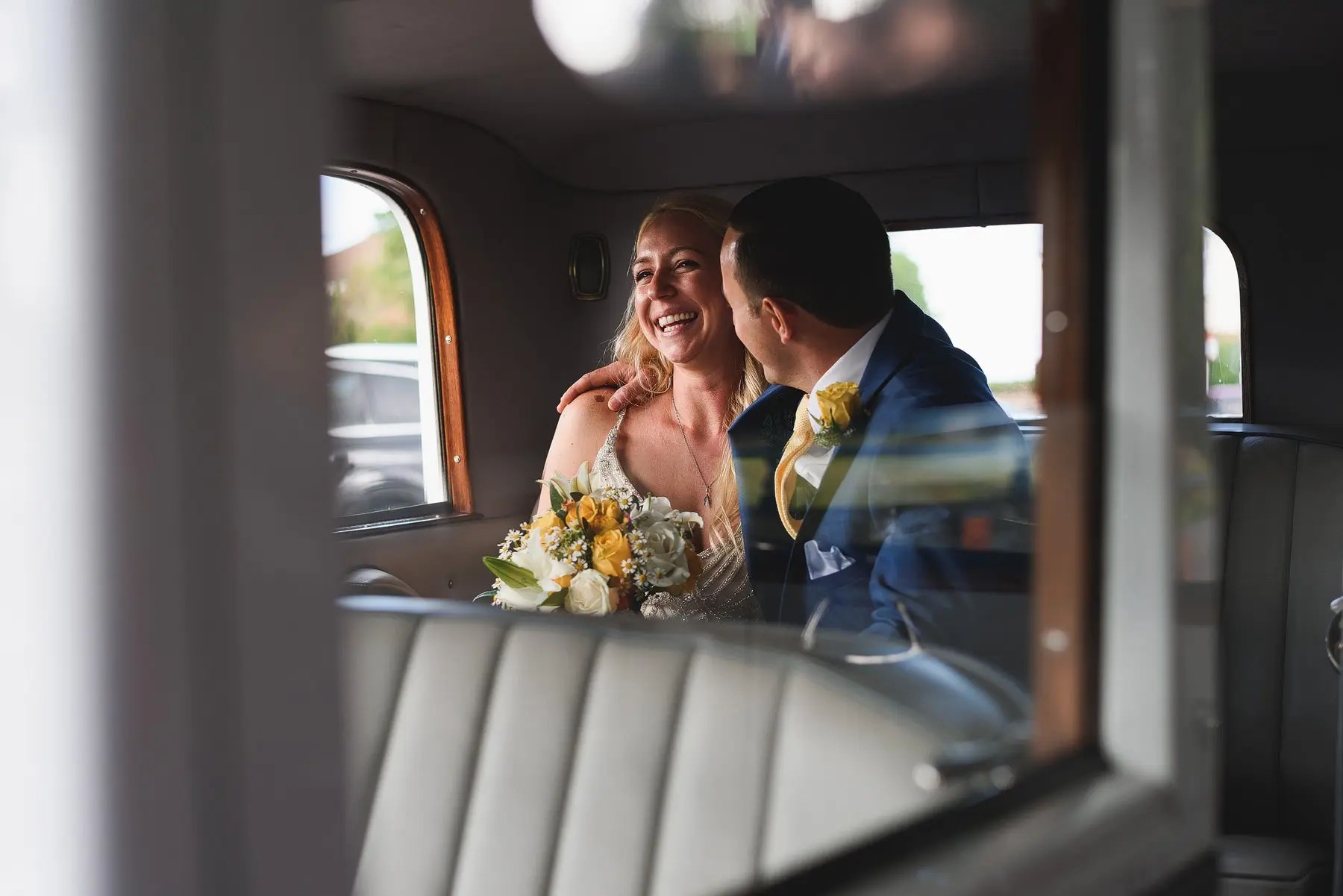 happy married couple in back of wedding car