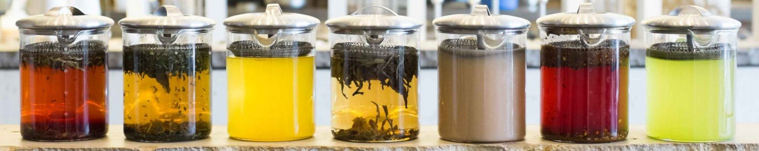 Seven different teas being brewed in glass teapots