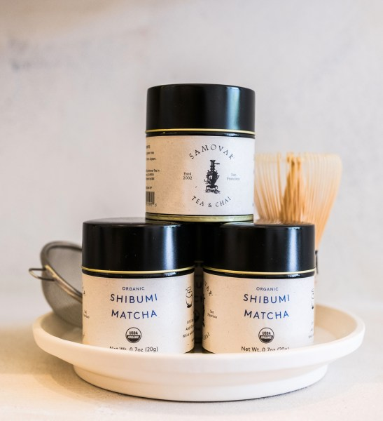 A stack of three Shibumi Matcha 20g tins are on a plate next to a matcha whisk and sifter.