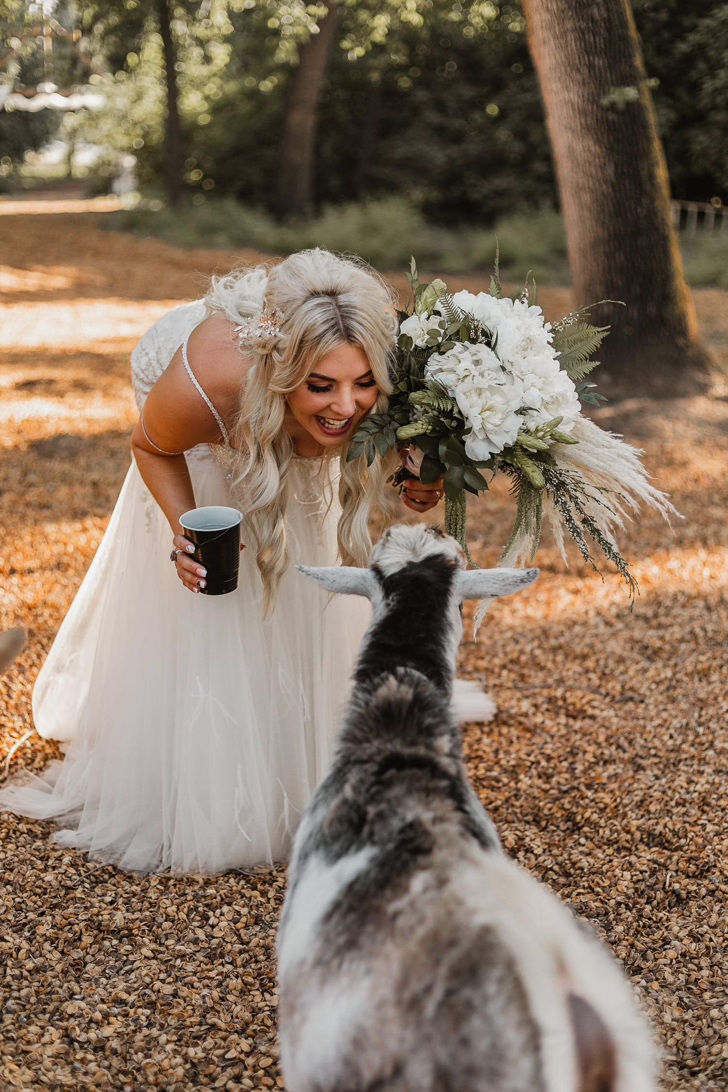 A Snow White bride kissing goats on the horse ranch.