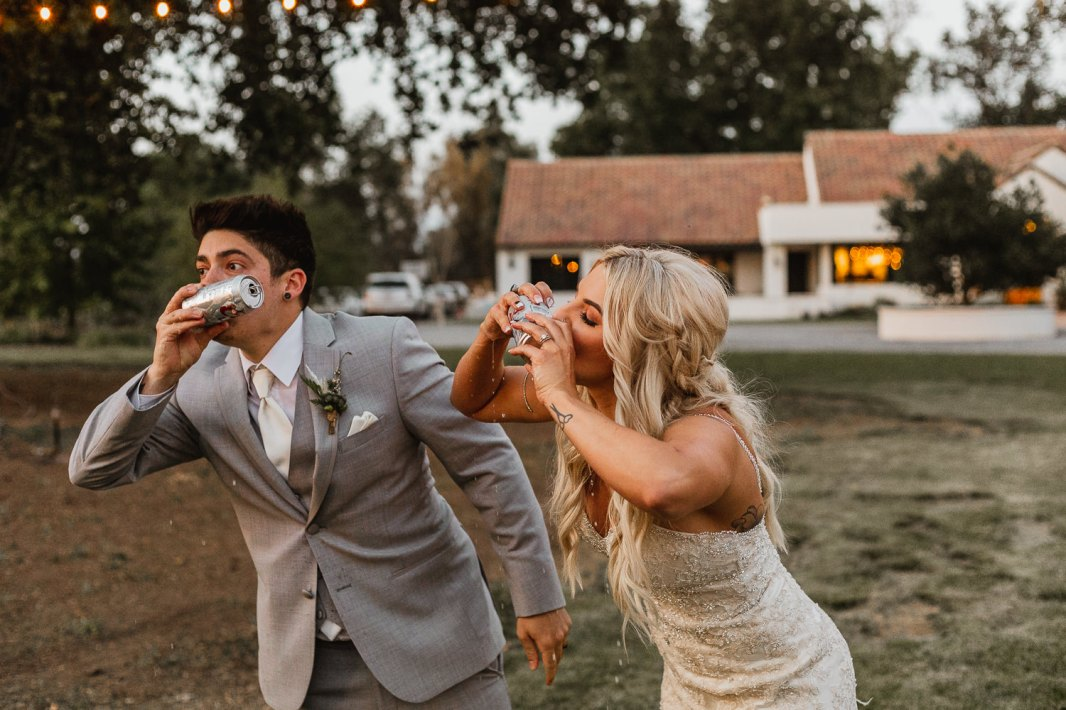 Bride and groom shotgunning beers.