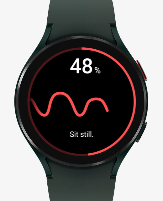 The front watch face of the Galaxy Watch4 device is measuring blood pressure. Its display changes from the blood pressure measuring feature to the ECG measuring feature.