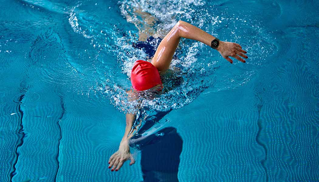 Icons of different exercises can be seen and the swimming icon is highlighted. A woman is swimming in a swimming pool while wearing a Galaxy Watch4 device.
