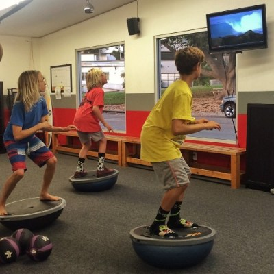 DSC groms try to stay in the best surf stance on a Bosu for the longest during an end-of-the-season challenge at the training headquarters. Photo: Courtesy Scott Kennaugh