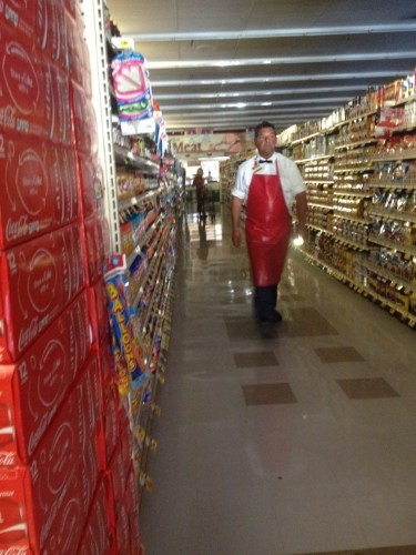 A grocer walks with a flashlight Friday afternoon through Stater Bros. in Capistrano Beach in Ocean View Plaza. Photo: Eric Heinz