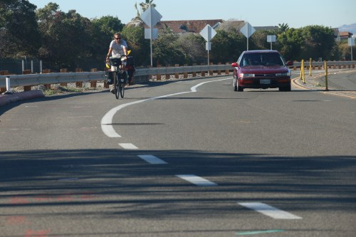 A cyclist rides next to a vehicle southbound on the Pacific Coast Highway on Tuesday. The improvements the city plans for would separate the bike lanes from traffic with a median and give two-way access for bicycles. Photo: Eric Heinz