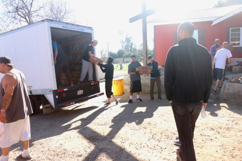 Men living at the ranch unload food supplies out of a truck on March 16 at Set Free Men's Ranch, just outside Lake Elsinore. Photo: Eric Heinz