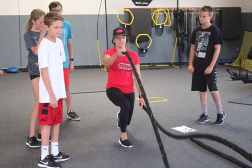 Chelsea Taylor, a LAB coach and former BYU track and field athlete, demonstrates proper technique to young athletes. Photo: Steve Breazeale