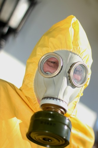 Public Watchdogs executive director Charles Langley dressed in a hazardous materials suit with a gas mask to highlight his organization's opposition to the storage of more spent nuclear fuel at San Onofre Nuclear Generating Station on Dec. 30 at a protest in San Clemente. Photo: Eric Heinz